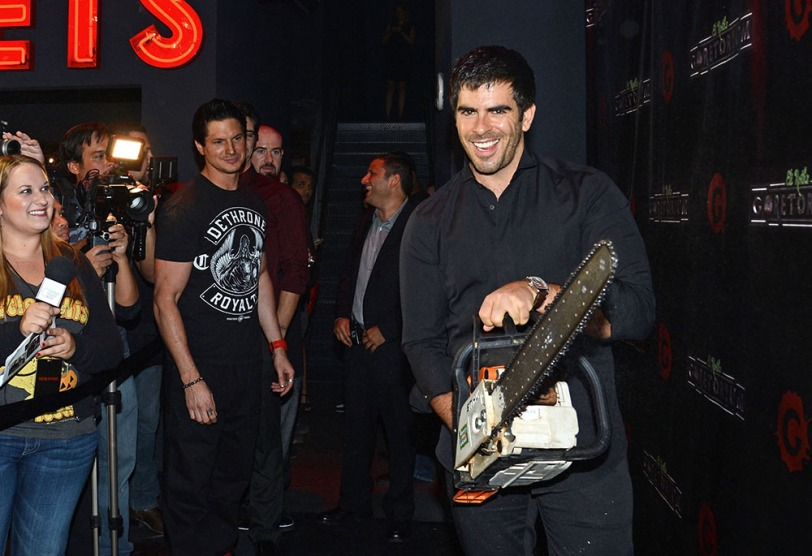 'Ghost Adventures' host Zak Bagans watches Eli Roth cut up the black carpet at the GORETORIUM grand opening.